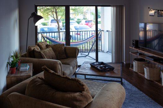 turned-off-flat-screen-tv-near-sofa-set-inside-white-room-1714430